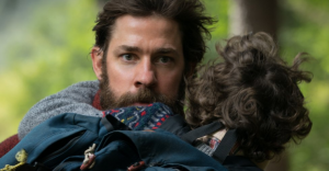 father carrying son and running in A Quiet Place movie