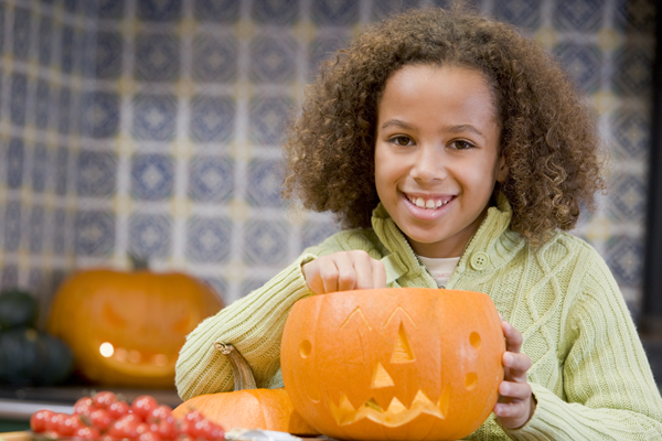 girl carving pumpkin on Halloween